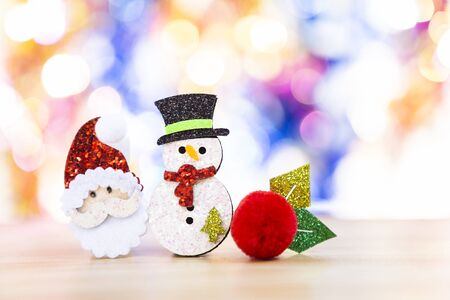 Snowman with cute Santa face over blurred bright colorful bokeh background, outdoor day light, Christmas concept background