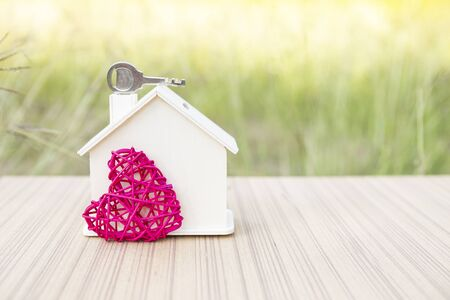 House key on wooden house with pink wooden heart over blurred green garden