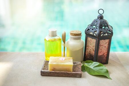 Spa concept background, Spa product body srub with herbal soap and vintage metal lamp over blurred swimming pool water background, outdoor day light