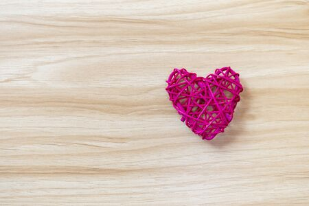 Design wooden pink heart on wood texture background, love and romance concept, valentine background