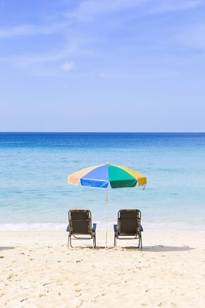 Summer concept background, beach chair and colorful umbrella on the beach with blue sea and clear sky view, holiday and vacation destination, outdoor day light