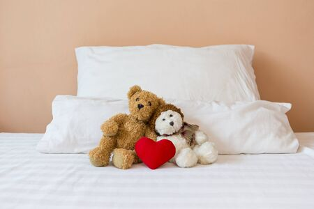 Two cute little teddy bear with red heart on the bed, love and romance concept, valentine background