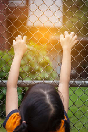 Girl hand on the wire fence, girl trying to escape, finding freedom 스톡 콘텐츠