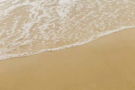 White wave on clear find brown sand beach, nature texture background, outdoor day light