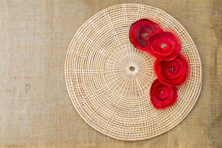 Red fabric rose flower on round rattan tray with space on hessian texture background, outdoor day light, decoration object Stok Fotoğraf