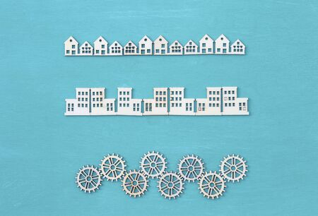 Wood veneer shape in house and building with wooden gears on blue texture background, decorate item for craft