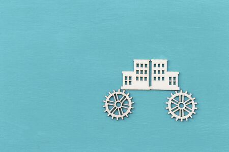 Building on wheel, wood veneer in building and gear shape on blue background, driving city concept