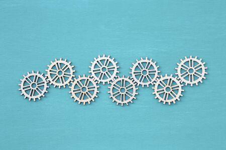Veneer wood cut in gear shape on blue texture background, industry concept