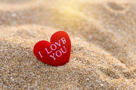 Coeur rouge avec message je t'aime sur la plage de sable, symbole d'amour et de romance, arrière-plan concept valentine
