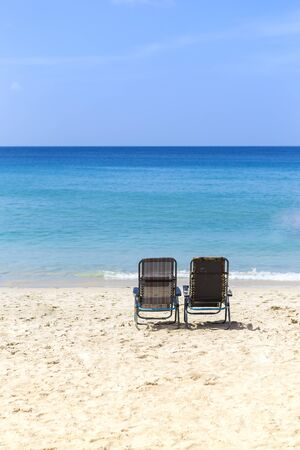 Beach chair on white sand over blue sea and clear blue sky, summer outdoor day light, relaxing by the sea, holiday and vacation destination