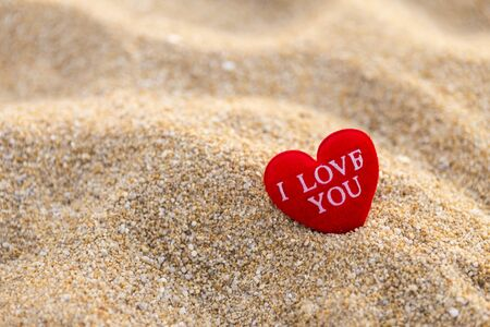 Message on red heart on sand beach, love and romance concept, valentine background idea, outdoor day light Stok Fotoğraf