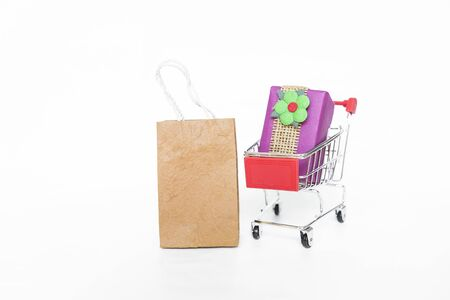 Paper shopping bag with gift in shopping cart isolate on white background, buying gift, delivery gift Stok Fotoğraf