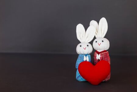 Two fabric rabbit doll in traditional Japanese dress with red heart with space on dark background, love and romance concept, valentine background idea