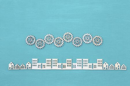 Wooden gears and wooden city on blue texture background, craft city, veneer wood cut in house shape and gear