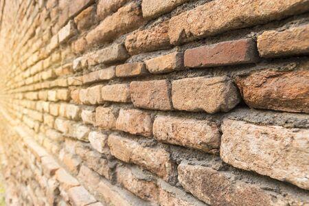 Closeup old brick wall background, vintage warm light