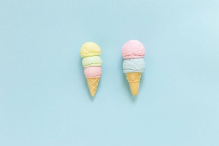 Pastel color ice cream cone on blue paper texture background, summer treat, small ice cream, handmade food craft object Stok Fotoğraf