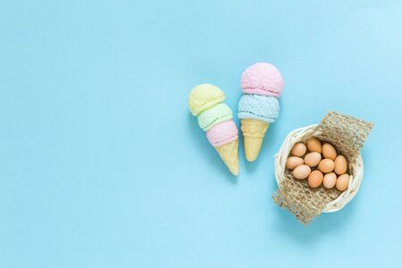 Colorful ice cream and egg in the basket on blue paper texture background, miniature food collection, handmade toy