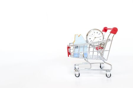 Vintage watch with miniature blue house in shopping cart isolate on white background, buying time and new house, property and real estate business