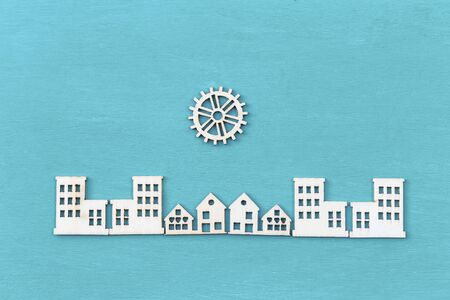 Veneer wood cut in building and gear shape arrange on blue texture background, industry city concept, wood craft item