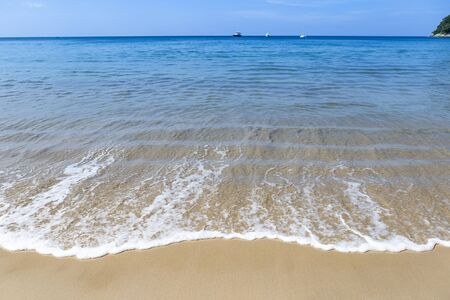 White wave on the clean sand beach, summer outdoor day light, clear sea water and blue sky, holiday relaxation Stok Fotoğraf