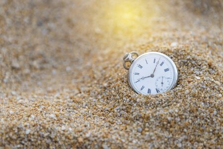 Vintage watch on sand with vintage warm light, time and sand, ancient watch on sand hill