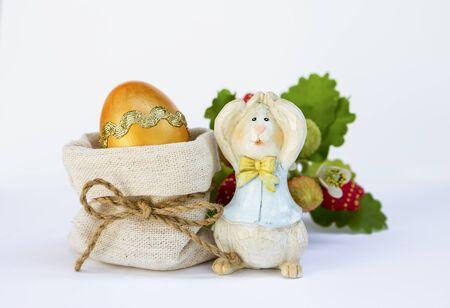 Golden Easter egg in canvas bag and Easter bunny over white background Reklamní fotografie