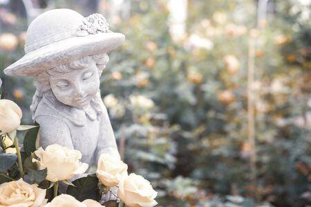 Girl sculpture with white rose over blurred flower garden, vintage tone style, garden decorate, spring and summer garden