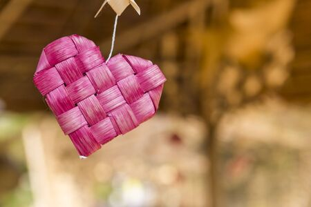 Pink bamboo wood heart over blurred background, love and romance concept, valentine background idea, craft item Reklamní fotografie