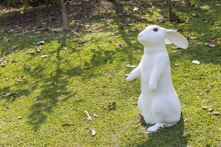 White rabbit sculpture staning on the green lawn, outdoor day light, garden decoration item
