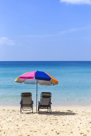 Beach chairs under colorful umbrella on the sand beach looking at the clean blue sea, holiday and vacation break destination, summer outdoor day light Reklamní fotografie