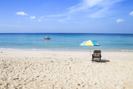 Relaxing on the beach on summer holiday break, outdoor day light, paradise island, beach chair undr umbrella looking at blue sea