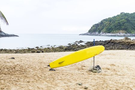 Yellow surfboard on the sand beach with the rock beach at the background, water sport and activity Reklamní fotografie