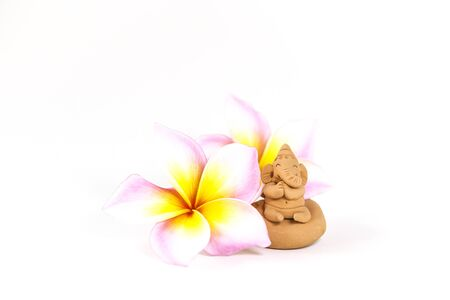 Praying cut elephant clay sculpture with beautiful plumeria flower isolate on white background, prey for the world, happy elephant