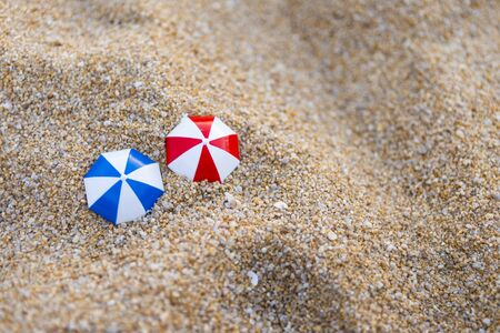 Red and blue plastic umbrella on sand background, environmental concept, outdoor day light
