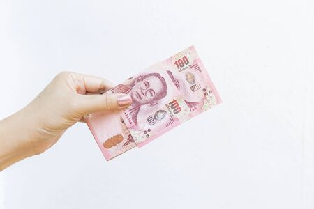 Girl hand holding bank note on white background, finance and banking concept, outdoor day light, investment and saving, Thai money, money exchange