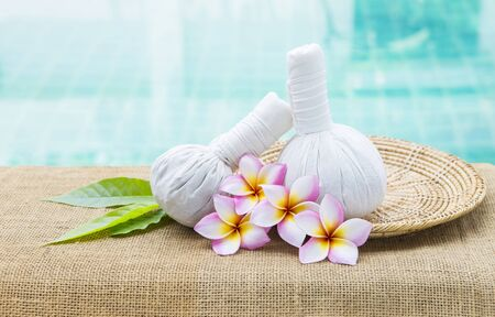 Spa concept background, handmade herbal massage ball with beautiful Plumeria flower on wooden tray over blurred blue water background, health care and wellness, outdoor day light