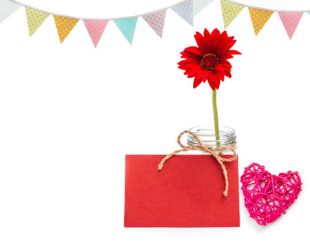 Red flower with red paper card with wooden pink heart and vintage party flag on white backgorund, valentine concept