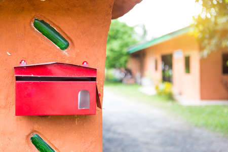 Red metal mail box on design clay wall over blurred house background, outdoor day light Stok Fotoğraf - 155340752