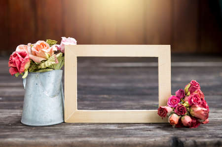 Wooden picture frame with rose paper flower in tinpot over blurred wood background with vintage warm light Stok Fotoğraf - 155443850