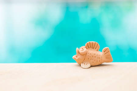 Cute little fish clay over blurred blue water background, clay sculpture for garden decroation