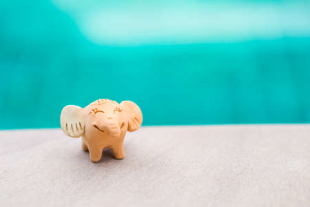 Little cute happy elephant clay doll on swimming pool edge with space on blurred blue water background, handmade toy