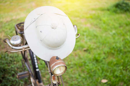 Traditional Thai style hat on old bicycle with space blurred green lawan, outdoor day light, countryside life style Stok Fotoğraf