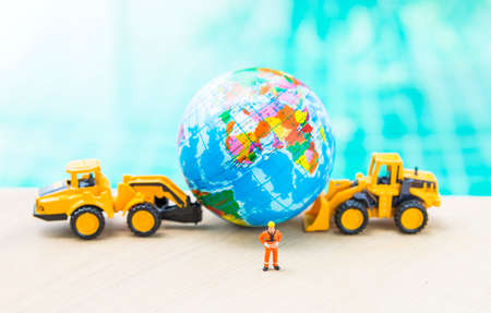 Moving world with yellow truck, miniature worker in safety suit over blurred globle ball and yellow truck, globle business