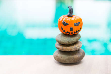 Halloween pumpkin with funny face on stack of stone over blurred blue water background, outdoor day light, happy halloween concept