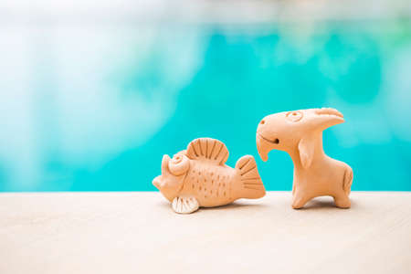 Fish and goat clay sculpture on swimming pool edge with space on blurred blue water background, outdoor day light, garden decoration item made from natural material