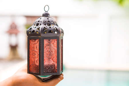 Simple design moroccan metal lamp in clay hand over blurred outdoor background, indoor house decoration item