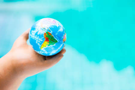 World map on global ball in clay hand over blurred blue water background, global warming and environmental Stok Fotoğraf