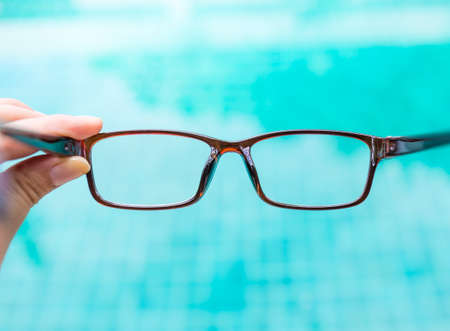 Eyeglasses in girl hand over blurred blue water background, reading glasses with plastic frame, women fashion eyeglasses