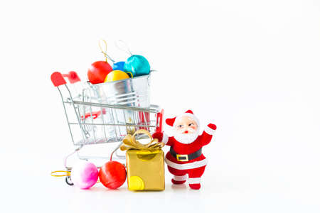 Christmas concept background, Santa doll and gift box with colorful ball for decoration in shopping cart on white background Stok Fotoğraf