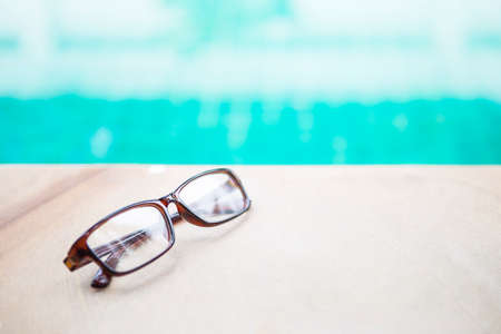 Eye glasses with brown frame on swimming pool edge over blurred blue water background, reading by the pool, outdoor day light